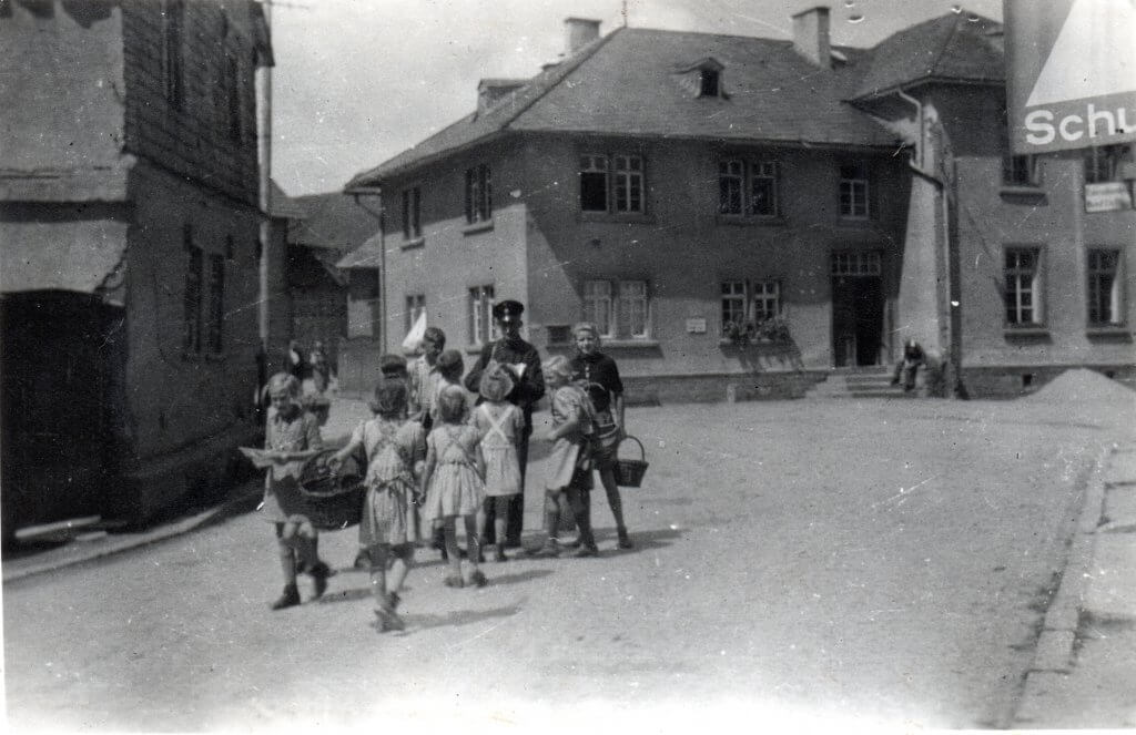 Postbote Julius Fischer mit Schulkindern auf der Hauptstraße (später Schwalbacher Straße). Im Hintergrund die Schule, links das Anwesen Leichtfuß / Rechener. Foto von Irmgard Pfeil.
